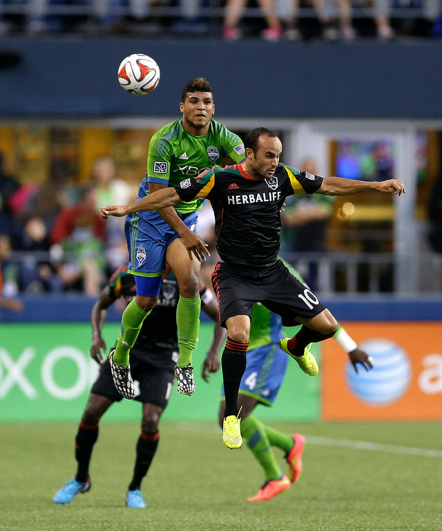 . Seattle Sounders\' DeAndre Yedlin, upper left, and Los Angeles Galaxy\'s Landon Donovan, right, go for a header in the second half of an MLS soccer match, Monday, July 28, 2014, in Seattle. Galaxy beat the Sounders 3-0. (AP Photo/Ted S. Warren)