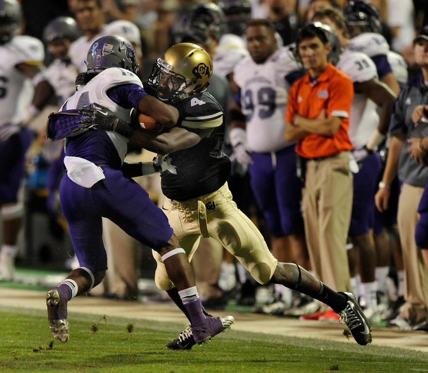 . BOULDER, CO. - SEPTEMBER 76: CU defensive back Chidobe Awuzie (4) stripped the ball from ACU receiver Jatavious Wilson (14) in the second half. The University of Colorado football team hosted Central Arkansas at Folsom Field Saturday night, September 7, 2013. Photo By Karl Gehring/The Denver Post