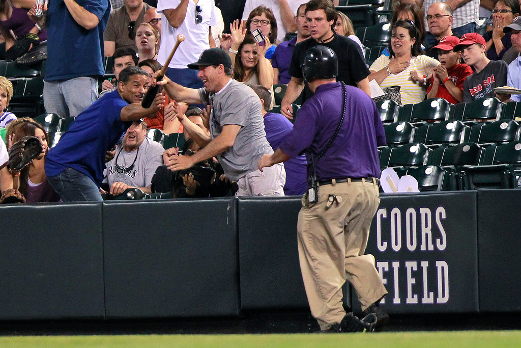 . Fans compete for a bat that flew into the stands after it slipped out of the hands of Colorado Rockies\' Carlos Gonzalez during the ninth inning of a baseball game between the Rockies and the Los Angeles Dodgers on Tuesday, July 2, 2013, in Denver. The Dodgers won 8-0. (AP Photo/Barry Gutierrez)