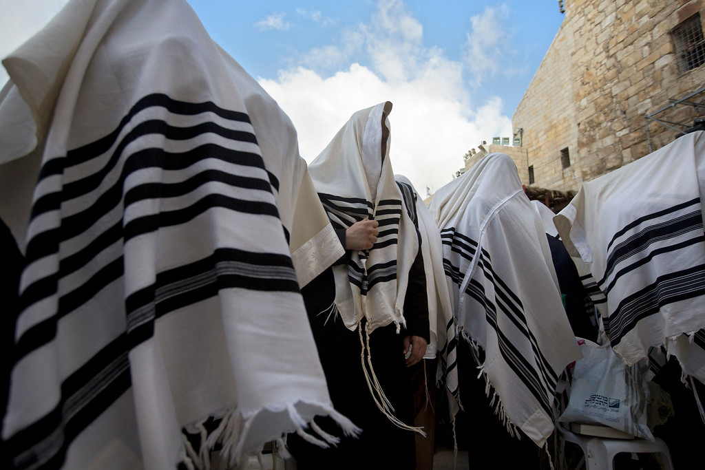 . Covered in prayer shawls, ultra-Orthodox Jewish men of the Cohanim Priestly caste participate in a blessing during the holiday of Sukkot, in front of the Western Wall, the holiest site where Jews can pray in Jerusalem\'s Old City, Sunday, Sept. 22, 2013 . The Cohanim, believed to be descendants of priests who served God in the Jewish Temple before it was destroyed, perform a blessing ceremony of the Jewish people three times a year during the festivals of Passover, Shavuot and Sukkot. (AP Photo/Sebastian Scheiner)