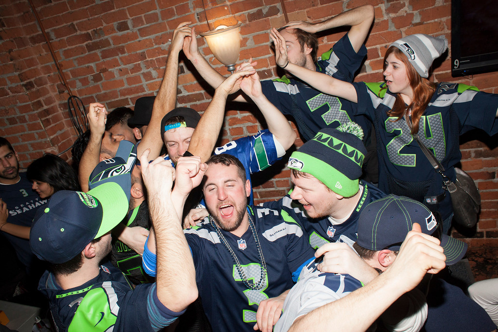 . Seattle Seahawks fans celebrate while watching the Super Bowl at Fuel, a bar on February 2, 2014 in Seattle, Washington. The Seahawks defeated the Denver Broncos 43-8 in Super Bowl XLVIII.  (Photo by David Ryder/Getty Images)