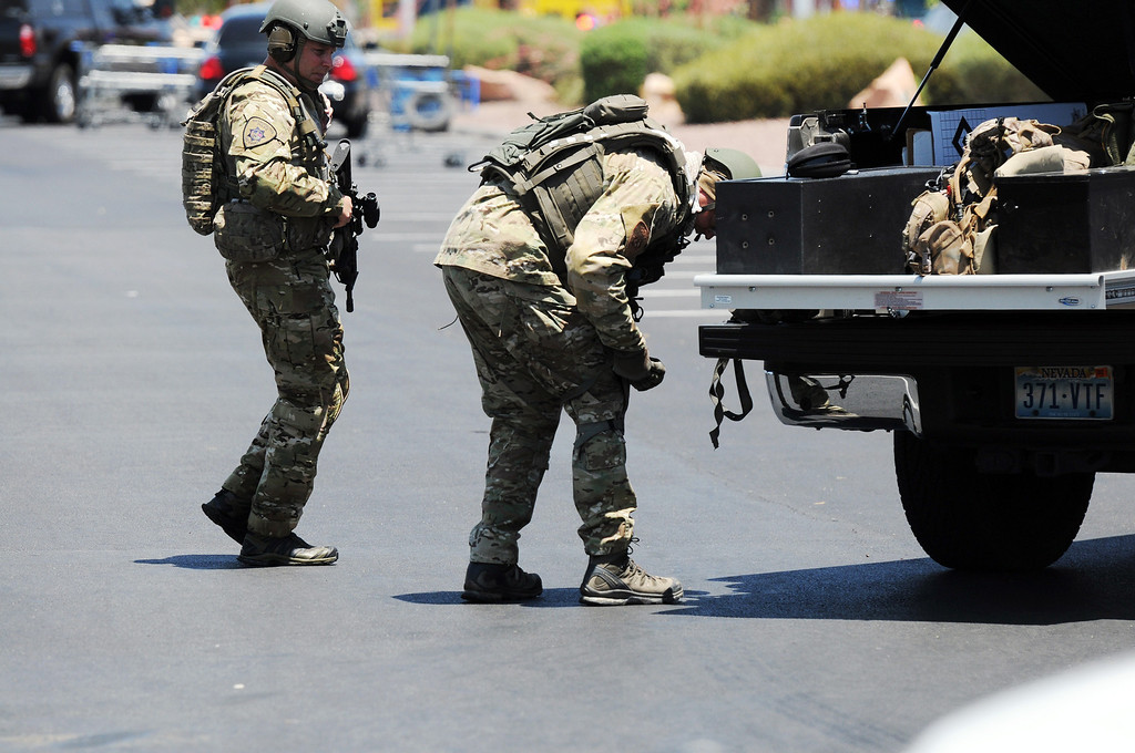 . Las Vegas police officers prepare to go near the scene of a shooting in Las Vegas, Sunday, June 8, 2014. The spree began around 11:30 a.m. Sunday when a man and woman walked into CiCi\'s Pizza and shot two officers who were eating lunch, Las Vegas police spokesman Larry Hadfield said. (AP Photo/Las Vegas Review-Journal, Eric Verduzco)