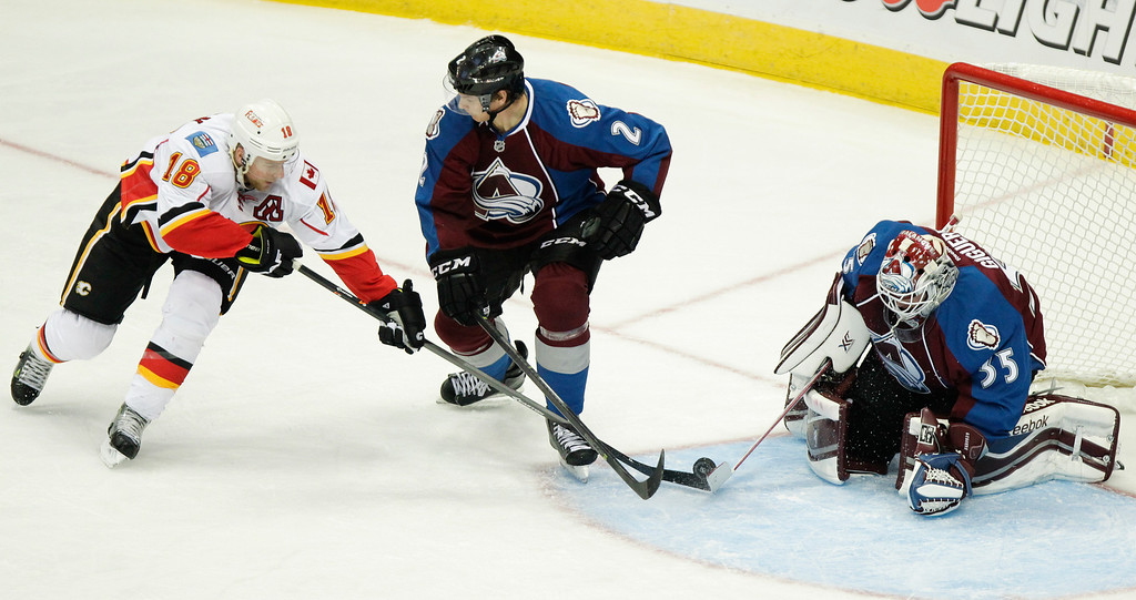 . Calgary Flames\' Matt Stajan (18) shoots with Colorado Avalanche\'s Nick Holden (2) and goalie Jean-Sebastien Giguere (35) defending during the third period of an NHL hockey game on Friday, Nov. 8, 2013, in Denver. The Avalanche won 4-2. (AP Photo/Barry Gutierrez)