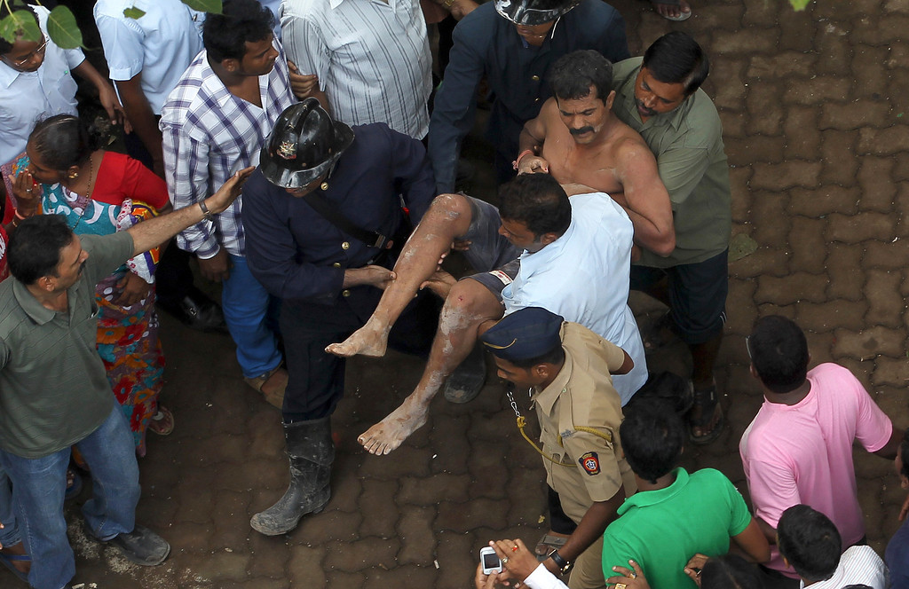 . Rescue workers carry an injured man from the rubble of a building that collapsed in Mumbai, India, Friday, Sept. 27, 2013.  (AP Photo/Rajanish Kakade)