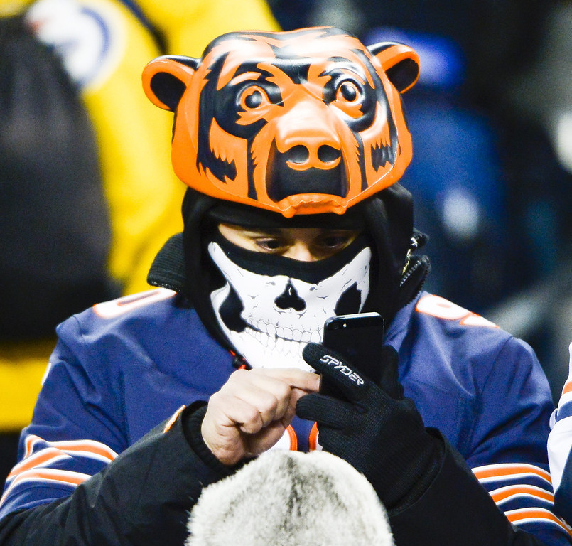. A Chicago Bears fan, bundled against the cold, uses a cell phone before the start of the first half of the Bears NFL game against the Dallas Cowboys at Soldier Field in Chicago, Illinois. EPA/TANNEN MAURY