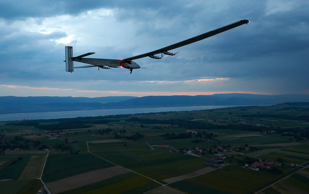 . German test pilot Markus Scherdel steers the solar-powered Solar Impulse 2 aircraft for its maiden flight at its base in Payerne, Switzerland early  Monday,  June 2, 2014. Picture taken from a helicopter.   (AP Photo/Denis Balibouse,Pool)