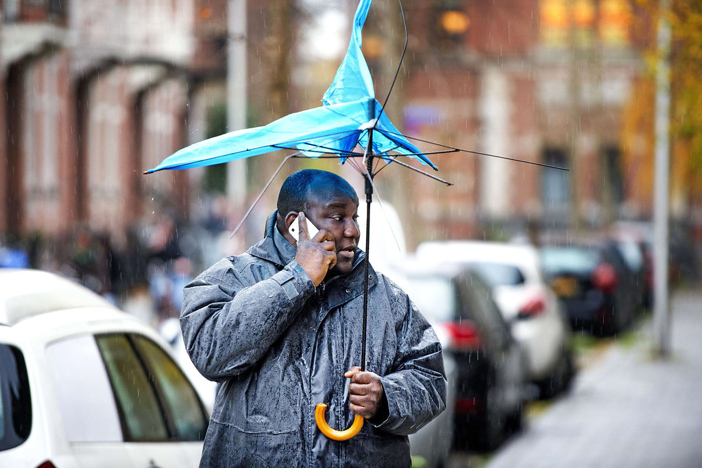 """. A man using his cellular phone walks while holding a broken umbrella on December 5, 2013 in Utrecht, The Netherlands. As forecasters sounded a \""""code orange\"""" extreme weather warning, The Netherlands is preparing for heavy storms with surging tides and winds predicted to gust up to 130 km/h (81 miles per hour) in places in the north. AFP PHOTO / ANP / ROBIN UTRECHT  *"""