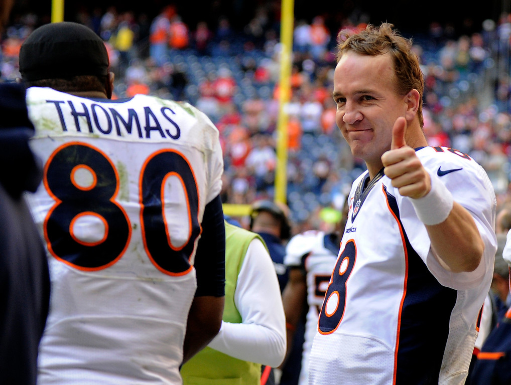 . Denver Broncos quarterback Peyton Manning (18) gives the thumbs up after talking to Broncos tight end Julius Thomas (80) on the bench after throwing his record breaking 51st pass to him for a touchdown in the fourth quarter against the Houston Texans December 22, 2013 at Reliant Stadium. (Photo by John Leyba/The Denver Post)