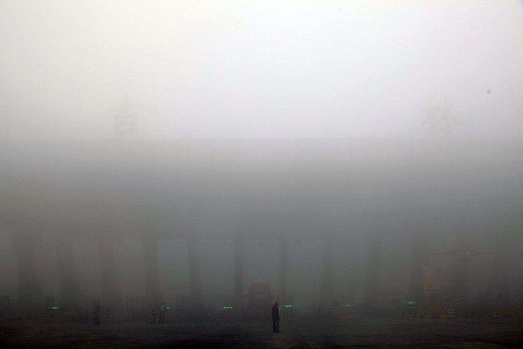 . A truck is seen waiting outside a toll booth after it is shuttered as heavy smog spreads on a highway as vehicles are forced to wait due to heavy smog in Jilin, northeast China\'s Jilin province on October 22, 2013.      AFP PHOTOSTR/AFP/Getty Images