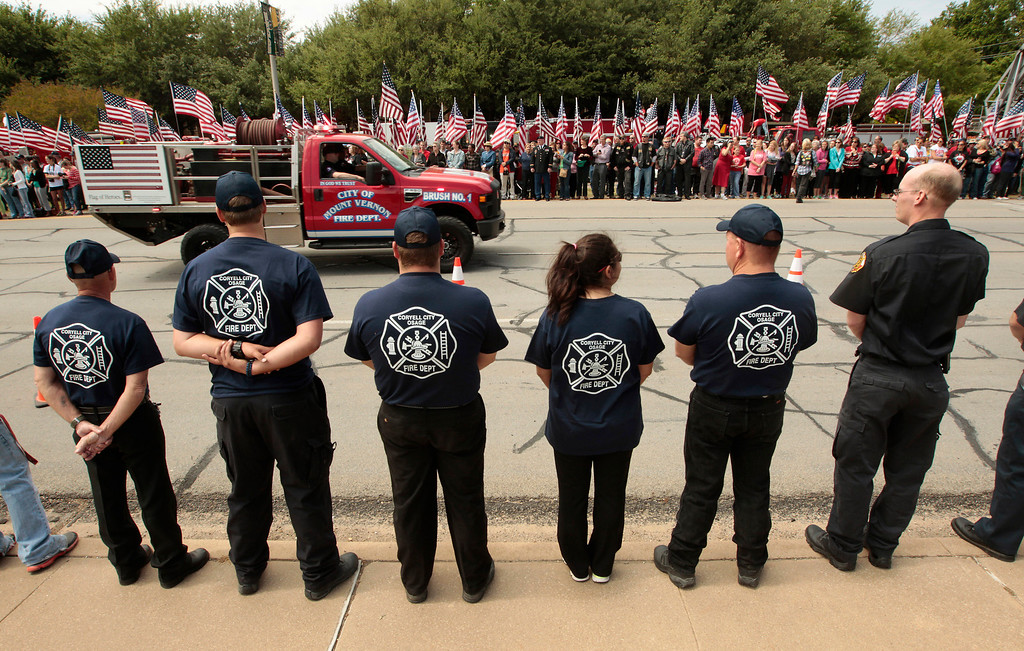 . Members of the Corvell City and Osage Volunteer Fire Department watch as fire departments from around Texas pay their respects during a parade for the West Memorial Service on April 25, 2013 in Waco, Texas. (Photo by Erich Schlegel/Getty Images)