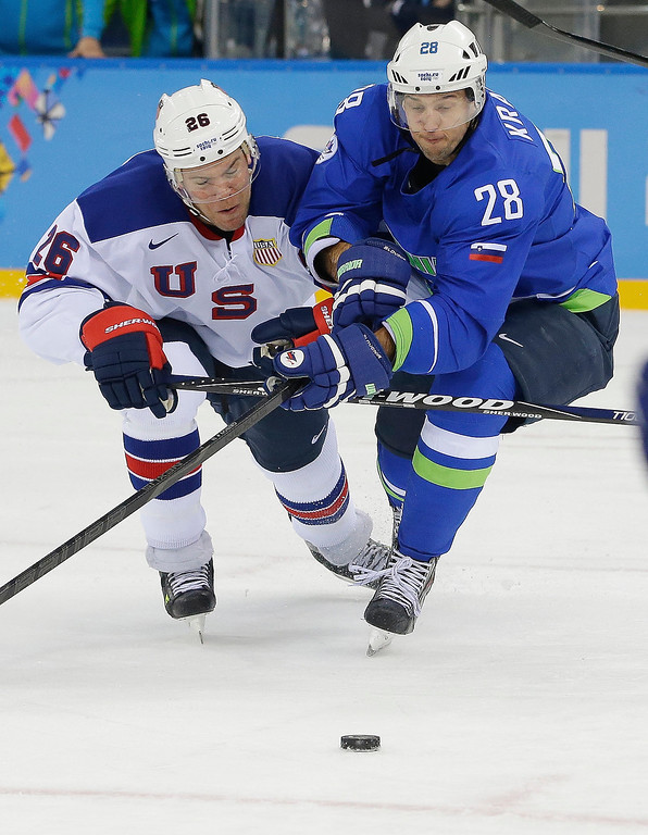 . USA forward Paul Stastny and Slovenia defenseman Ales Kranjc battle for control of the puck during the 2014 Winter Olympics men\'s ice hockey game at Shayba Arena Sunday, Feb. 16, 2014, in Sochi, Russia. (AP Photo/Matt Slocum)