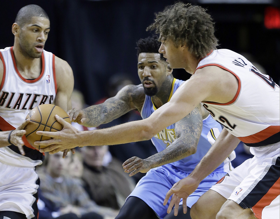 . Portland Trails Blazers center Robin Lopez, right, passes off to teammate Nicolas Batum, from France, left, as Denver Nuggets forward Wilson Chandler defends during the first half of an NBA basketball game in Portland, Ore., Thursday, Jan. 23, 2014. (AP Photo/Don Ryan)