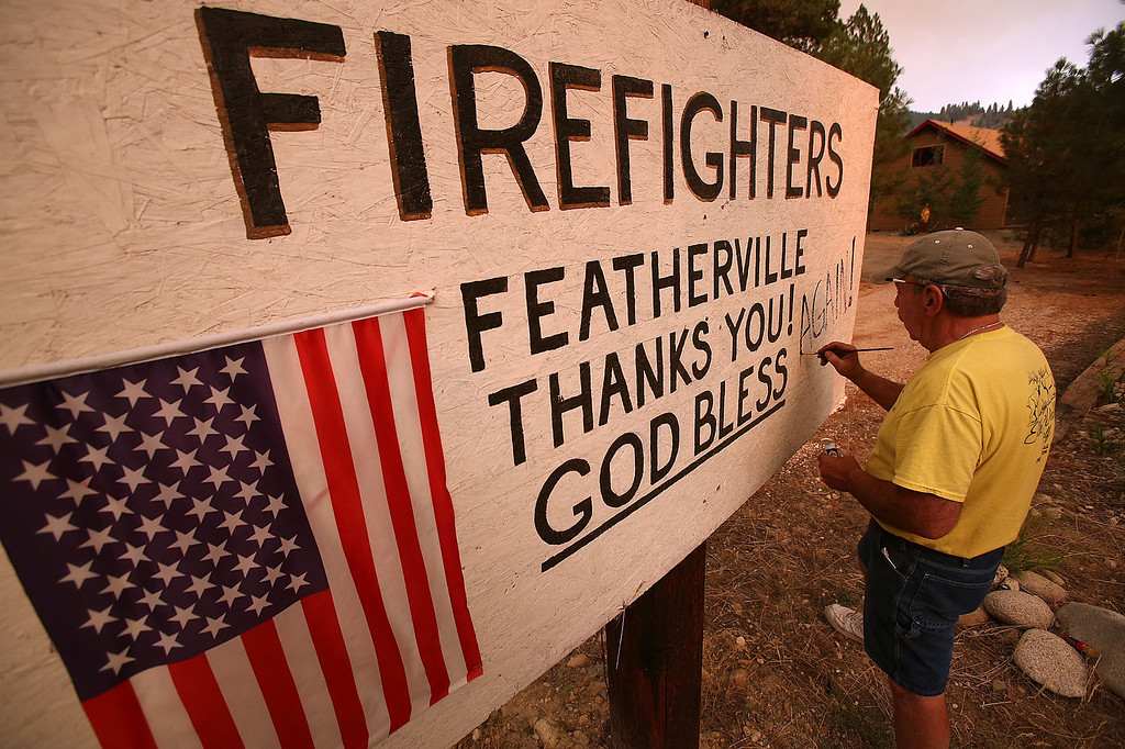 . John Lewis, of Featherville, works on a sign in town that greets firefighters battling the 111,000 acre Elk Complex Fire on Wednesday, Aug. 14, 2013. (AP Photo/Times-News, Ashley Smith)