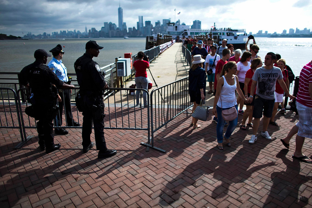 . A SWAT team member stands guard while people arrive to visit the Statue of Liberty and Liberty Island during its reopening to the public in New York July 4, 2013. The Statue of Liberty and Liberty Island opens to the public for the first time since Hurricane Sandy made landfall on October 29, 2012.  REUTERS/Eduardo Munoz