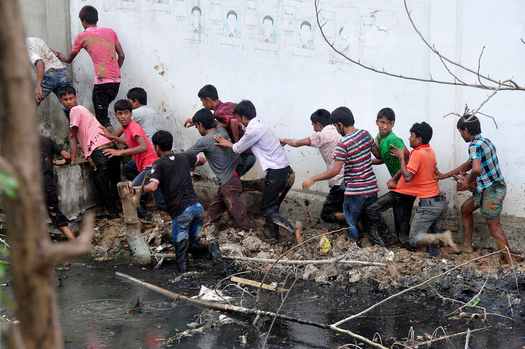 . Protesters run through a drain after police charge with batons during a demonstration in Savar, outside Dhaka April 30, 2013. REUTERS/Khurshed Rinku