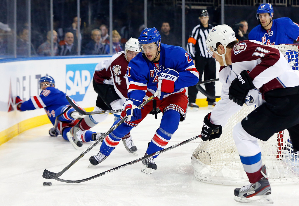 . Derek Stepan #21 of the New York Rangers clears the puck from behind the net against Jamie McGinn #11 of the Colorado Avalanche at Madison Square Garden on February 4, 2014 in New York City.  (Photo by Jim McIsaac/Getty Images)