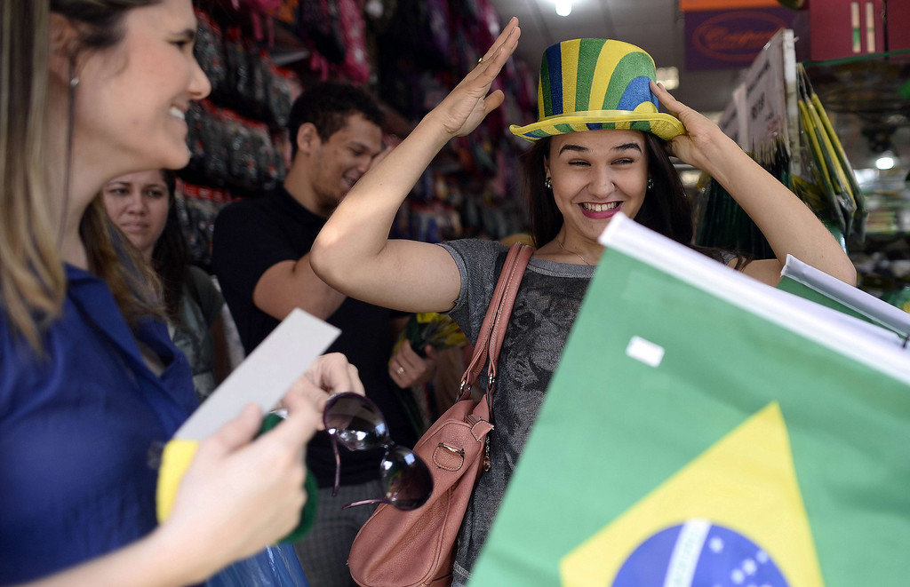 . A lady tries on a hat in a shop selling World Cup related merchandise in Ribeirao Preto on June 10, 2014, ahead of the 2014 FIFA World Cup in Brazil. AFP PHOTO / FRANCK  FIFE/AFP/Getty Images