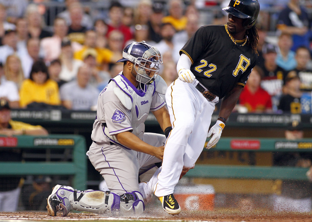 . PITTSBURGH, PA - AUGUST 03:  Andrew McCutchen #22 of the Pittsburgh Pirates is tagged out at home by Wilin Rosario #20 of the Colorado Rockies in the third inning during the game on August 3, 2013 at PNC Park in Pittsburgh, Pennsylvania.  (Photo by Justin K. Aller/Getty Images)