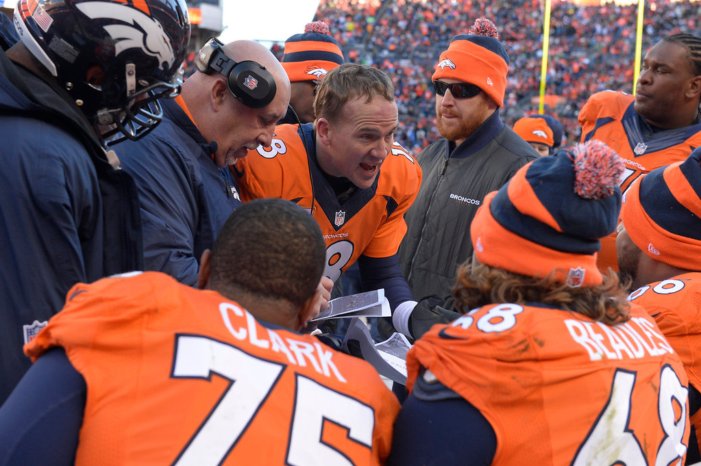 . Denver Broncos quarterback Peyton Manning (18) talks with his team on the sidelines in the second quarter. The Denver Broncos take on the San Diego Chargers at Sports Authority Field at Mile High in Denver on January 12, 2014. (Photo by Craig F. Walker/The Denver Post)