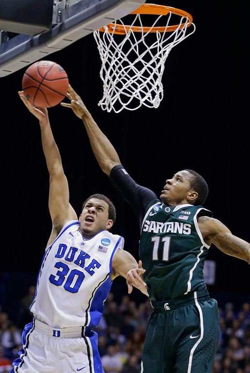 . Michigan State guard Keith Appling (11) blocks a shot by Duke guard Seth Curry (30) during the first half of a regional semifinal in the NCAA college basketball tournament, Friday, March 29, 2013, in Indianapolis. (AP Photo/Darron Cummings)