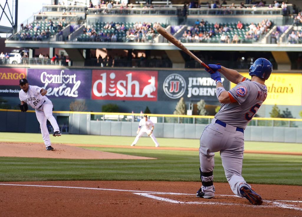 . New York Mets\' David Wright, front, follows the flight of his RBI-double on a pitch from Colorado Rockies starting pitcher Franklin Morales, left, in the first inning of a baseball game in Denver, Saturday, May 3, 2014. (AP Photo/David Zalubowski)