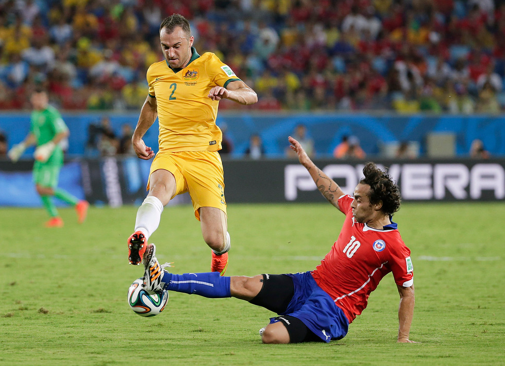 . Australia\'s Ivan Franjic is challenged by Chile\'s Jorge Valdivia, right, during the group B World Cup soccer match between Chile and Australia in the Arena Pantanal in Cuiaba, Brazil, Friday, June 13, 2014.  (AP Photo/Felipe Dana)