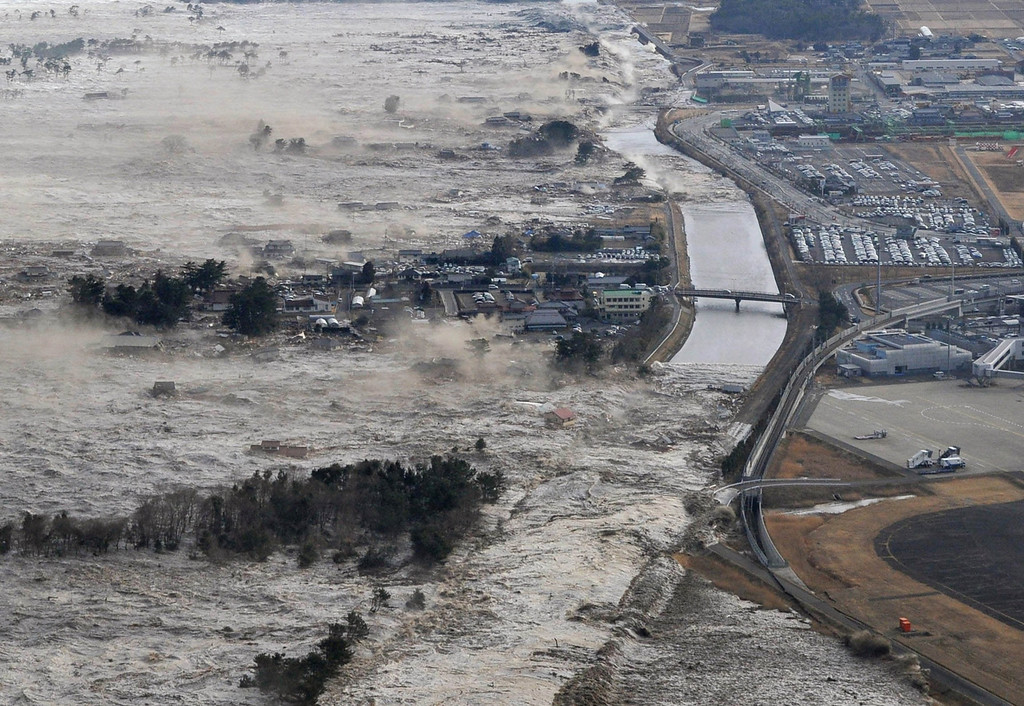 . Earthquake-triggered tsunami waves sweep along Iwanuma in northern Japan on Friday March 11, 2011. The magnitude 8.9 earthquake slammed Japan\'s eastern coast Friday, unleashing a 13-foot (4-meter) tsunami that swept boats, cars, buildings and tons of debris miles inland. (AP Photo/Kyodo News)