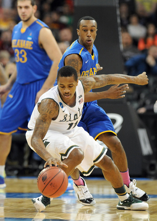 . Keith Appling #11 of the Michigan State Spartans tries to keep control of the ball while guarded by Jarvis Threatt #4 of the Delaware Fightin Blue Hens during the second round of the 2014 NCAA Men\'s Basketball Tournament at Spokane Veterans Memorial Arena on March 20, 2014 in Spokane, Washington.  (Photo by Steve Dykes/Getty Images)