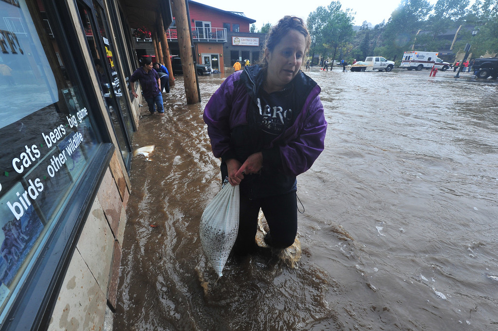 . Volunteers slog through dirty water to place sandbags along east Elkhorn Avenue on Thursday night, Sept 12, 2013. Walt Hester/Estes Park Trail-Gazette