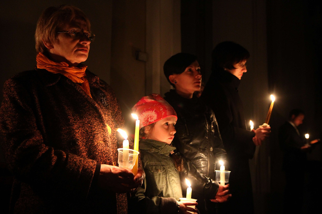 . People light candles during an Easter vigil mass in the Cathedral in Vilnius, Lithuania,on April 19, 2014. AFP PHOTO / PETRAS MALUKAS/AFP/Getty Images