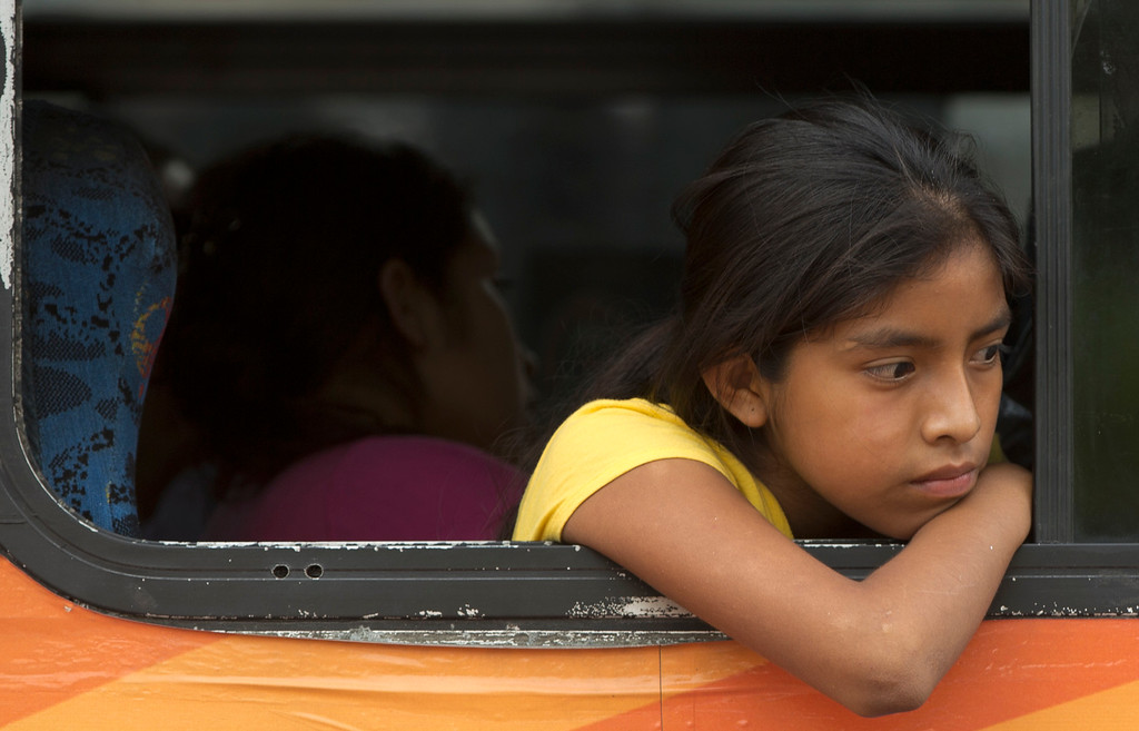 . A young resident from the village La Pintada leans out a bus window as she waits to be driven from a temporary shelter at the convention center to another shelter, in Acapulco, Mexico, Thursday, Sept. 19, 2013. Federal police rescued more than 300 people from La Pintada after it was hit by a landslide Monday afternoon. It was the biggest known tragedy caused by twin weekend storms that struck Mexico, creating floods and landslides across the nation and killing at least 97 people as of Thursday - not counting those missing in La Pintada. (AP Photo/Eduardo Verdugo)