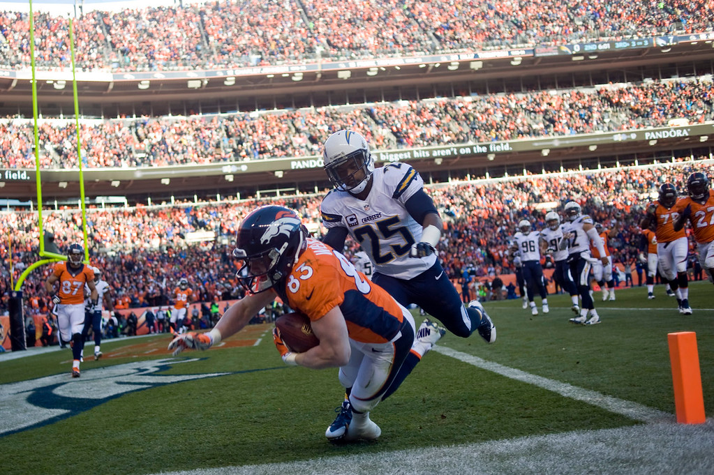 . Denver Broncos wide receiver Wes Welker (83) takes the ball into the end zone on a second quarter touchdown pass over San Diego Chargers defensive back Darrell Stuckey (25). The Denver Broncos vs. The San Diego Chargers in an AFC Divisional Playoff game at Sports Authority Field at Mile High in Denver on January 12, 2014. (Photo by Patrick Traylor/The Denver Post)