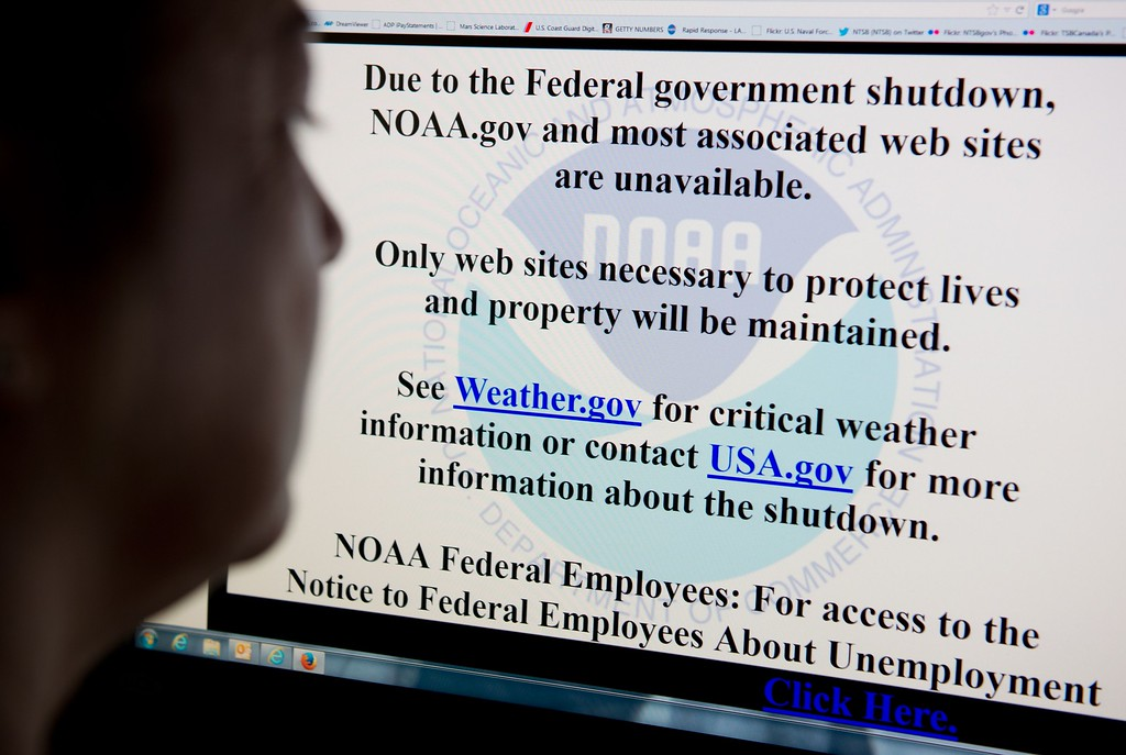 . A woman reads a notice of closure on the National Oceanic and Atmospheric Administration internet site from Washington, DC on October 2, 2013. As part of the US federal government shutdown many non-essential sites run by government agencies will remain static, replaced with a splash page. AFP PHOTO / Karen BLEIER/AFP/Getty Images