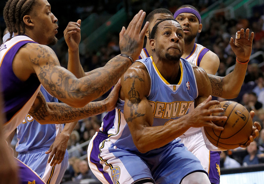 . Denver Nuggets\' Andre Iguodala tries to drive against Phoenix Suns\' Michel Beasley, left, and Jared Dudley, right, during the first half of an NBA basketball game, Monday, March 11, 2013, in Phoenix. (AP Photo/Matt York)
