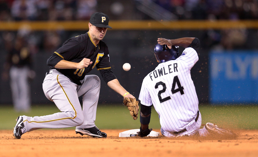 . Colorado Rockies\' Dexter Fowler (24) steals second base as the ball bounces away from PIttsburgh Pirates shortstop Jordy Mercer in the third inning of a baseball game in Denver, Saturday, Aug. 10, 2013. (AP Photo/Joe Mahoney)