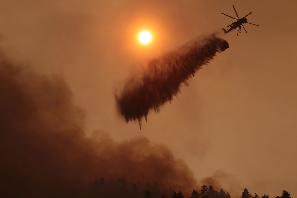 . As fire rolls down a ridge towards homes, a helicopter drops water on the more than 90,000-acre Elk Fire Complex burning near Pine, Idaho, on Monday, Aug. 12, 2013. (AP Photo/Times-News, Ashley Smith)