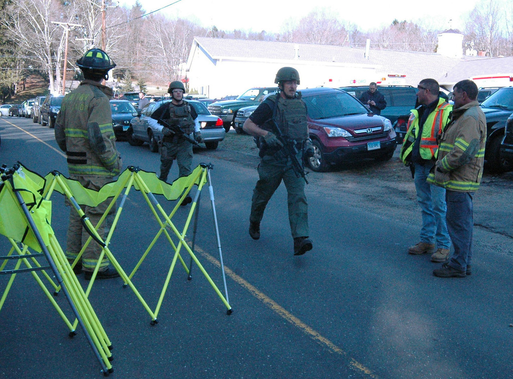 . In this photo provided by the Newtown Bee, police officers are on the scene outside Sandy Hook Elementary School in Newtown, Conn., where authorities say a gunman opened fire, killing 26 people, including 20 children, Friday, Dec. 14, 2012. (AP Photo/Newtown Bee, Shannon Hicks)