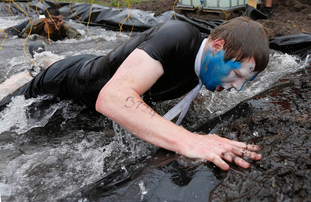 """. A participant of the \""""Tough Mudder\"""" endurance event series crawls out of the \""""Electric Eel\"""" obstacle in the Fursten Forest, a former British Army training ground near the north-western German city of Osnabrueck July 13, 2013. The hardcore but un-timed event over 16 km (10 miles) was designed by British Special Forces to test mental as well as physical strength. Some 4,000 competitors had to overcome obstacles of common human fears, such as fire, water, electricity and heights.   REUTERS/Wolfgang Rattay"""