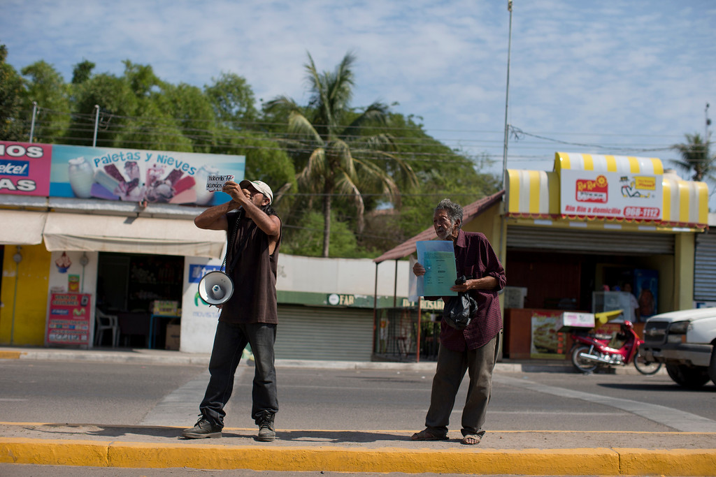 . In this June 12, 2013 photo, a preacher and a beggar stand on the old Durango-Mazatlan road, at the entrance to the town of Concordia, Mexico.  A new Durango-Mazatlan highway will pass through colonial Concordia, founded in 1565 by the Spaniards as a way station between the coast and the gold mines. Government officials say the new road will bring legitimate economy to a troubled area. Locals say it may improve access, or take what little honest business they had as trucks and buses bypass towns altogether.(AP Photo/Dario Lopez-Mills)