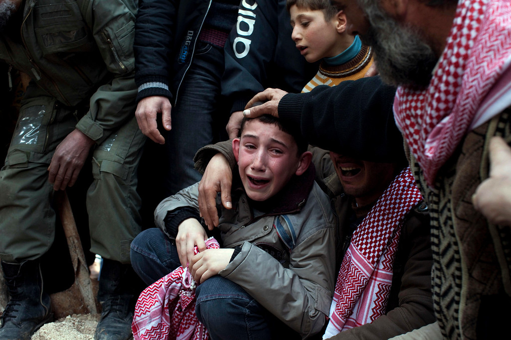 . FILE - Ahmed, center, mourns his father Abdulaziz Abu Ahmed Khrer, who was killed by a Syrian Army sniper, during his funeral in Idlib, north Syria, Thursday, March 8, 2012. (AP Photo/Rodrigo Abd, File)