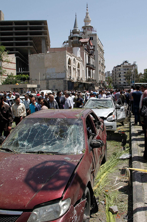 . People walk on a street lined with damaged cars after a blast at Marjeh Square in Damascus April 30, 2013. The bomb in central Damascus killed 13 people on Tuesday, state television said, a day after Prime Minister Wael al-Halki survived an attack on his convoy in the heart of the Syrian capital. State television said 70 people were wounded, several critically. The British-based Syrian Observatory reported 9 dead civilians and 3 security men and said the death toll was likely to rise.   REUTERS/Khaled al-Hariri