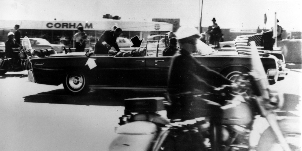 . Secret Service agent Clint Hill climbs into the back seat of the limousine a moment after Kennedy and Gov. Connally were shot.  The black arrow points to Nellie Connally, who is ducking bullets. The white arrow points out the agent\'s foot, mistakenly thought to be the president\'s when the photo first ran.  Associated Press file