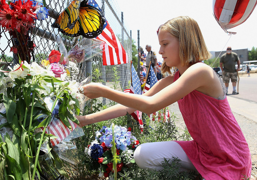. Shelby Blocker of Prescott, AZ leaves flowers at a memorial set up outside of Station 7 on July 1, 2013 in Prescott, Arizona.  Station 7 has been the home of the Granite Mountain Interagency Hotshot Crew since 2010, and is a national resource that responds to wildland and all risk incidents in the Prescott Basin.  (Photo by Christian Petersen/Getty Images)