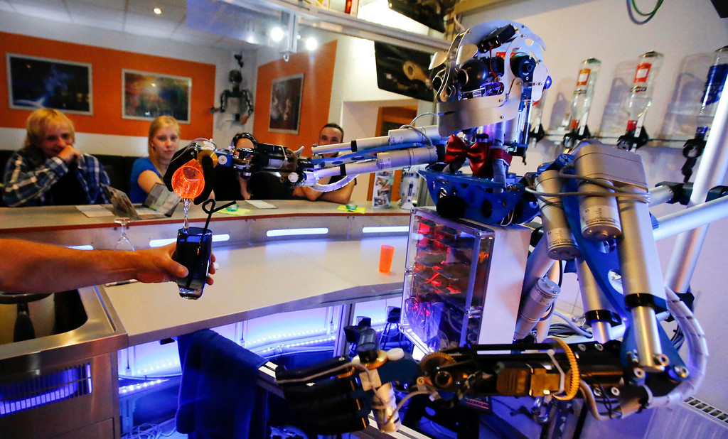 """. Humanoid robot bartender \""""Carl\"""" pours a spirit into the cocktail shaker of a bartender to prepare a drink for a guest at the Robots Bar and Lounge in the eastern German town of Ilmenau, July 26, 2013. \""""Carl\"""" - developed and built by mechatronics engineer Ben Schaefer who runs a company for humanoid robots - prepares spirits for the mixing of cocktails and is able to interact with customers in small conversations. Picture taken July 26, 2013. REUTERS/Fabrizio Bensch"""
