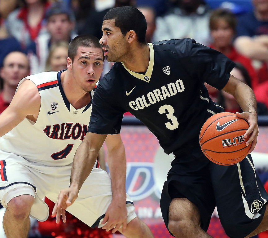 . Xavier Talton #3 of the Colorado Buffaloes handles the ball guarded by T.J. McConnell #4 of the Arizona Wildcats during the first half of the college basketball game at McKale Center on January 23, 2014 in Tucson, Arizona.  (Photo by Christian Petersen/Getty Images)