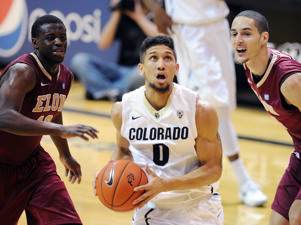 . Askia Booker drives to the basket for two against Austin Hamilton and Sebastian Koch, both of  Elon, during the second half of the December 13, 2013 game in Boulder. (Cliff Grassmick/Boulder Daily Camera)
