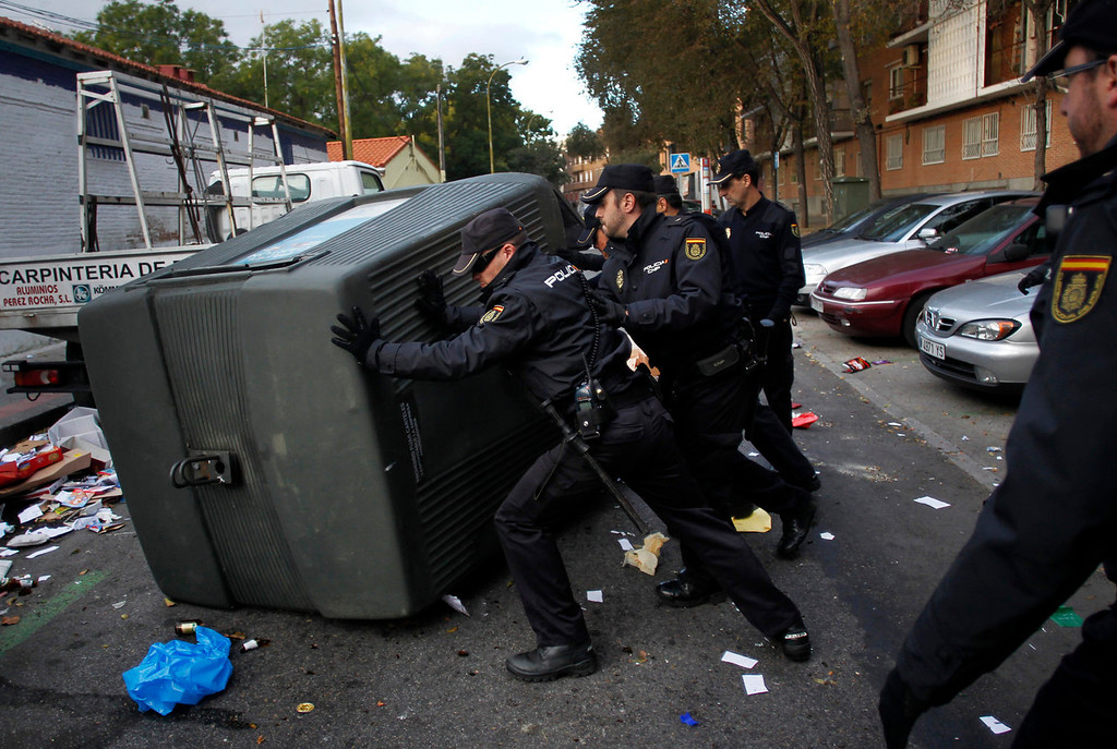 . Spanish police officers push back a trash container that was blocking the street after it was tipped over during picket action outside a road sweeper\'s coordination centre in Madrid, Tuesday, Nov. 5, 2013. Street cleaners and garbage collectors who work in the city\'s public parks walked off the job at midnight in a strike called by trade unions to contest the planned layoff of more than 1,000 workers. Madrid\'s municipal cleaning companies, which have service supply contracts with the city authorities, employ some 6,000 staff. (AP Photo/Francisco Seco)