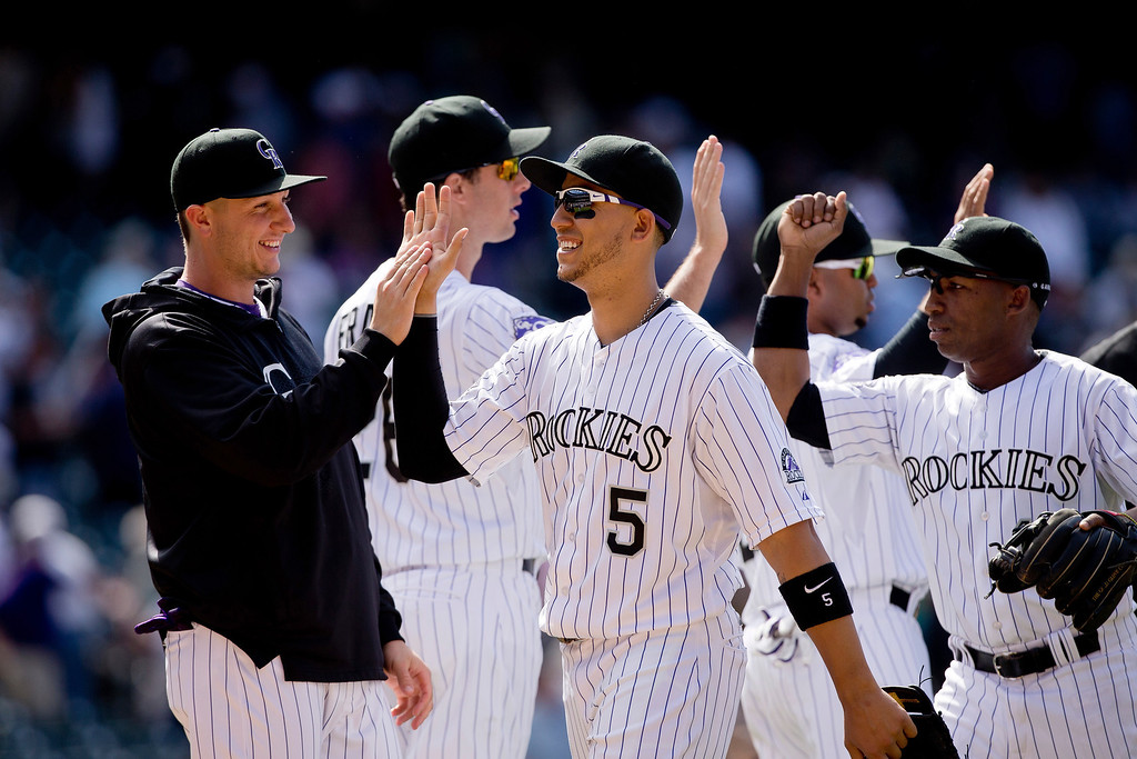 . Carlos Gonzalez #5 of the Colorado Rockies celebrates as he walks off the field with teammate Troy Tulowitzki #2 after the Rockies defeated the Diamondbacks 4-1 at Coors Field on May 22, 2013 in Denver, Colorado.  (Photo by Justin Edmonds/Getty Images)