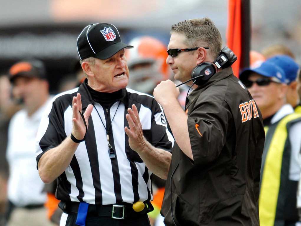 . Field judge Scott Steenson, left, explains a call to Cleveland Browns head coach Rob Chudzinski in the second quarter of an NFL football game against the Cincinnati Bengals Sunday, Sept. 29, 2013, in Cleveland. (AP Photo/David Richard)