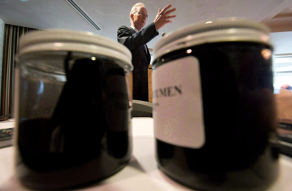 . Raw bitumen and diluted bitumen are displayed in jars as newspaper publisher David Black speaks during a news conference in Vancouver, on Aug. 17, 2012.    (AP Photo/The Canadian Press, Darryl Dyck)